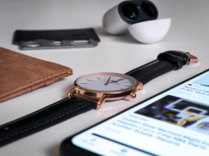 brown leather bifold wallet beside black leather strap gold round analog watch